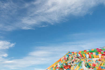Clear sky with white clouds floating,peacefully.With a tower consist of a lot of colorful prayer flags in the corner as foreground in the morning in Tibet,China.