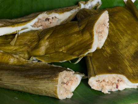 Indian sweet made of steamed rice flour filled with jaggery, cardamom and coconut. Wrapped in turmeric leaves and steam cooked in large vessel. Traditional food of Mangalore, Karnataka, locally called patholi in the Konkani language.