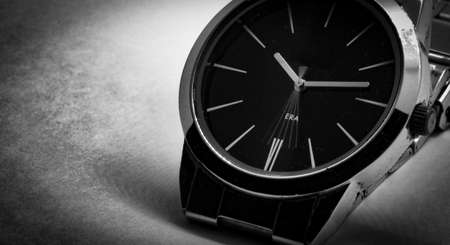 Black and white macro photo of a wrist watch with the letters era behind the moving second hand.