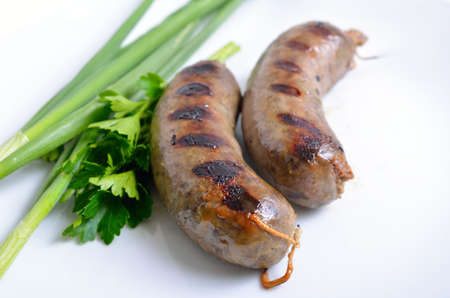 Grilled homemade liver sausage with greens on white plate.