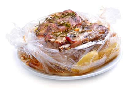 Baked meat packaged in a sleeve for baking. Pork belly with greens. Isolated on white background.