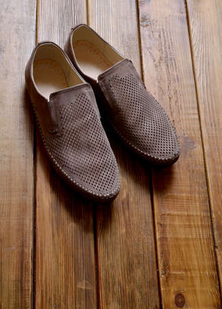 Leather mens shoes with perforation on the wooden background.