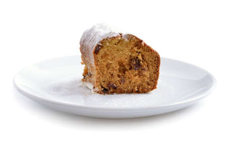 Piece of cake with raisin on the white plate. Isolated.
