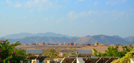 Solar PV modules and solar hot water panels mounted on rooftops. In Egyptian hotel. Itbay or Atbay Mountain on background.