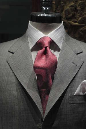 밝은 회색 바둑판 무늬 셔츠와 빨간색 무늬 넥타이와 회색 재킷의 근접 스톡 콘텐츠
