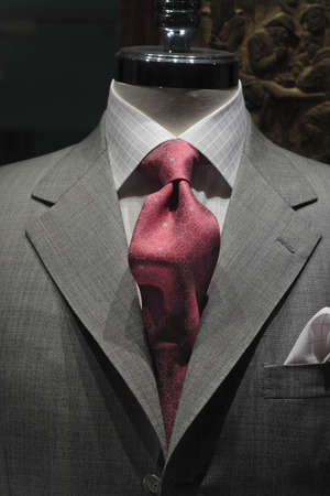 coat and tie: Close-up of a grey jacket with light grey checkered shirt and red patterned tie Stock Photo