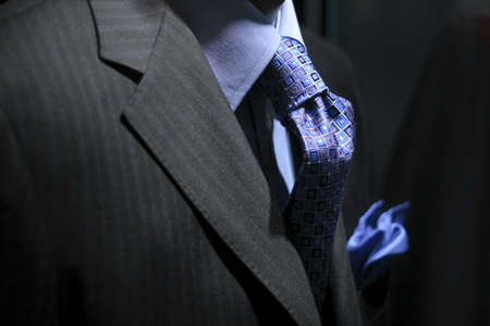 Close up of a dark grey striped jacket with blue shirt, tie & handkerchief