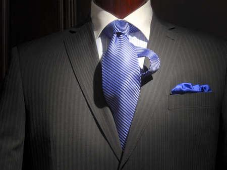 traje: Primer plano de una chaqueta de rayas color gris oscura con camisa de rayas azul con cuello blanco, corbata a rayas azul y pa�uelo azul