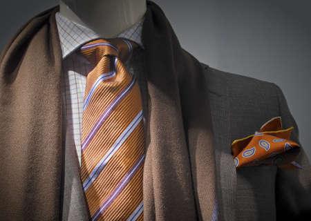 갈색 스카프, 흰색 바둑판 무늬 셔츠, 오렌지 스트라이프 넥타이, 손수건으로 회색 재킷의 근접 촬영
