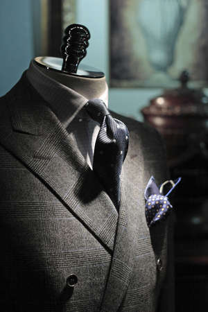 Close-up of grey checkered jacket with white checkered shirt, dark blue tie and handkerchief