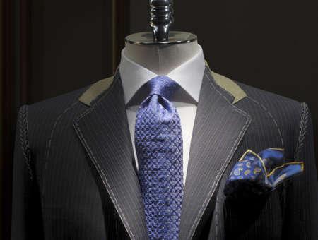 op maat: Onvoltooide jas met witte steken, wit overhemd, patroon blauwe strop das en zak doek  Stockfoto