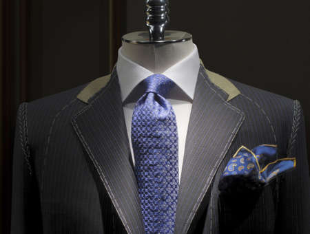 blue grey coat: Unfinished jacket with white thread stitches, white shirt, patterned blue tie and handkerchief