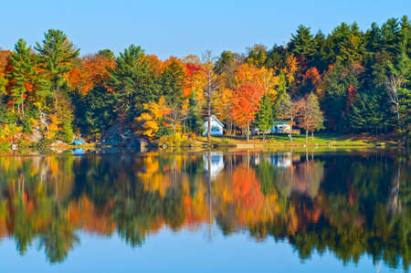 Autumn landscape with colourful trees reflecting in a calm lake. Stock Photo