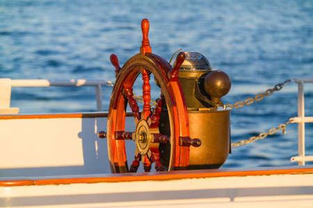 helm boat: Rueda de timón y brújula en un barco de vela antiguo viejo iluminado por la luz del atardecer.