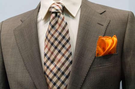 흰색 셔츠, 갈색 체크 무늬 넥타이와 오렌지 손수건 밝은 회색 체크 무늬 재킷의 근접