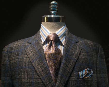 어두운 갈색과 파란색 체크 무늬 재킷, 스트라이프 셔츠, 자주색 넥타이와 손수건 마네킹