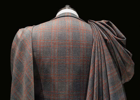 Rear close up view of a mannequin in checkered suit with fabric folds pinned to the shoulder photo