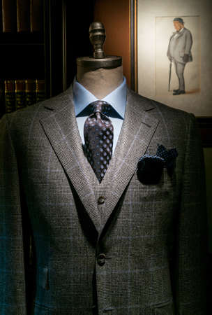menswear: Mannequin in gray checkered suit, blue shirt, dark tie and handkerchief