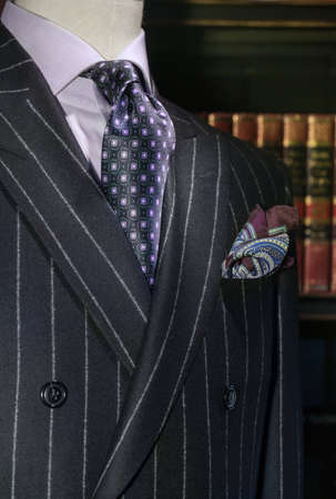menswear: Mannequin in dark striped double-breasted jacket, purple shirt, patterned black   purple tie and handkerchief  Bookshelves on the background