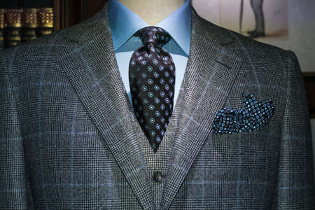 Mannequin in gray checkered suit, blue shirt, dark tie and handkerchief  photo