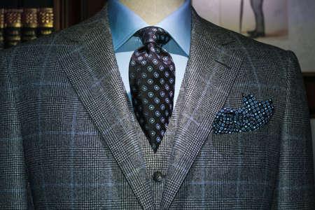 suit coat: Mannequin in gray checkered suit, blue shirt, dark tie and handkerchief