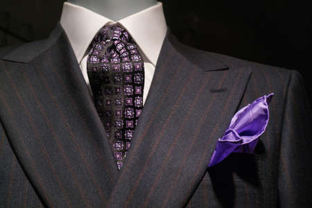 Close up of a dark gray striped jacked with white shirt, patterned black   purple tie and purple handkerchief