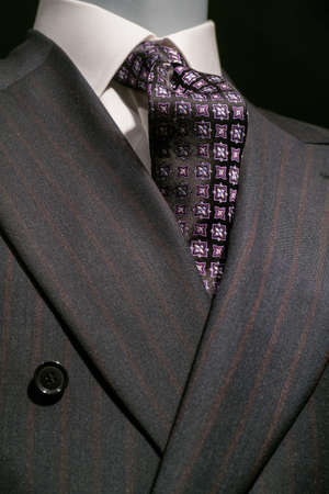 Close up of a dark gray striped jacked with white shirt and patterned black   purple tie  photo