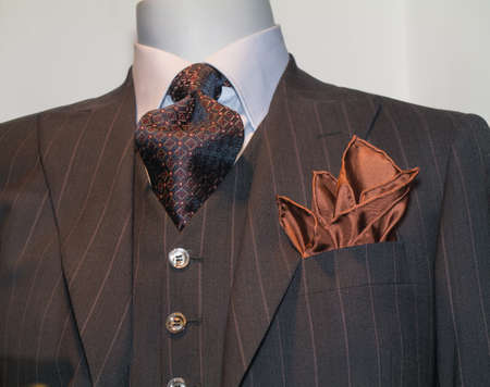 menswear: Close up of a dark brown striped jacked with patterned black   red tie and tan handkerchief