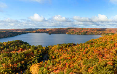 Autumn landscape panorama with colourful forest, lake, sky and clouds  photo