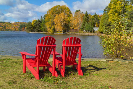 adirondack chair: Two red Adirondack Chairs on a lake shore on a sunny autumn day