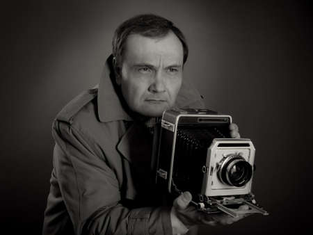 Zwart-wit foto van een retro persfotograaf met een oude camera