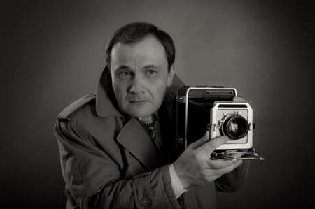 photo shooting: Black and white photo of a retro press photographer with an old camera