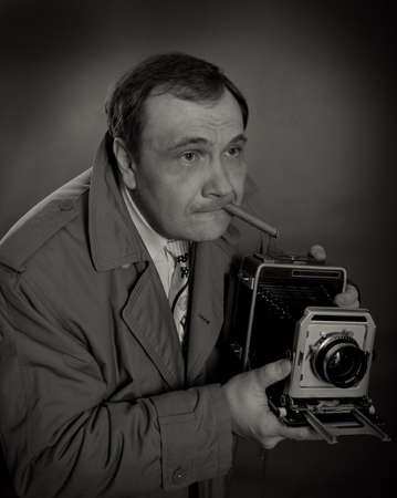 photojournalist: Black and white photo of a retro press photographer with an old camera and a sigar