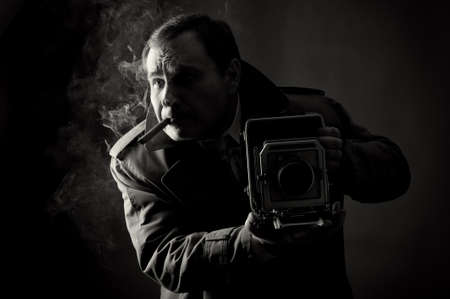 cigar smoke: Black and white contrast photo of a retro press photographer with an old camera smoking a sigar  Stock Photo