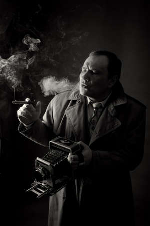 vintage foto: Zwart-wit contrast foto van een retro persfotograaf met een oude camera het roken van een sigaar
