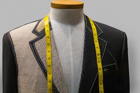 Onvoltooide zwarte jas met witte draad steken en geel meetlint Stockfoto