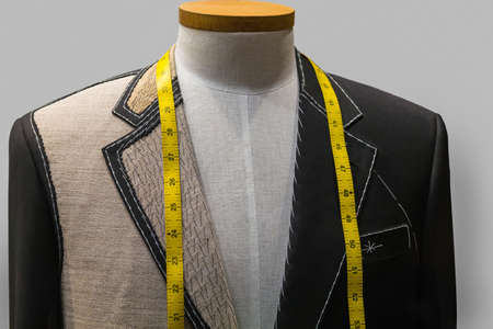 tailor shop: Unfinished black jacket with white thread stitches and yellow measuring tape