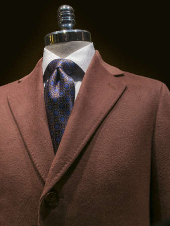 menswear: Close up of a brown cashmere coat with white striped shirt and blue patterned tie on a black background  Clipping path included