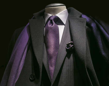 menswear: Close-up of a black coat, black jacket, white shirt, purple tie and scarf  Stock Photo
