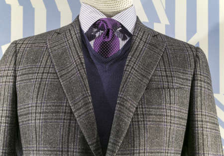stripe: Close up of a grey checkered jacket with blue v-neck sweater and purple tie  Stock Photo