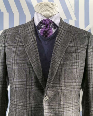 tailor suit: Close up of a grey checkered jacket with blue v-neck sweater and purple tie  Stock Photo