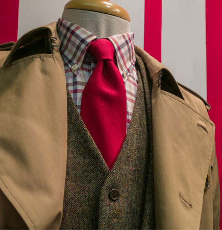 menswear: Close-ip of a tan raincoat   suit, checkered shirt and red tie