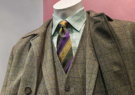 Close-up of a grey   yellow checkered coat and suit with light green checkered shirt and striped tie  photo