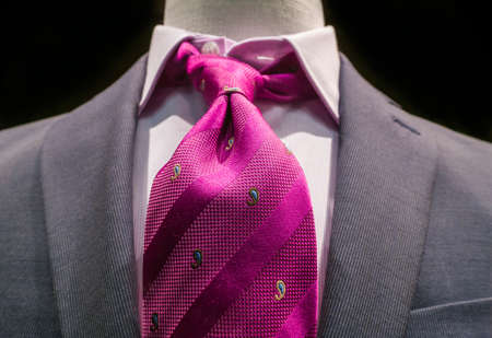 Close-up of a grey jacket with white striped shirt and bright magenta tie on black background  photo