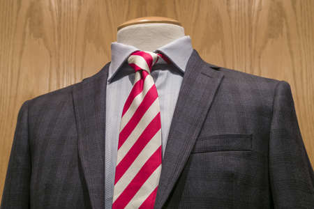 Close-up of a dark grey jacket with white textured shirt and red   white striped tie on a wooden background  Clipping path included  photo