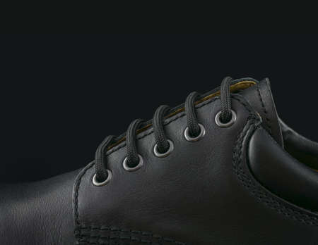 walk in closet: Extreme close-up of a black men s shoe on black background with copy space  Stock Photo