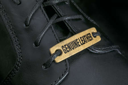 genuine leather: Extreme close-up of a black men s shoe with  Genuine Leather  tag