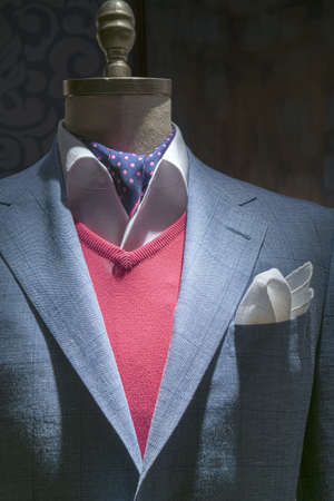 menswear: Close-up of a light blue checkered jacket with red sweater, white shirt, blue polka dots tie and white handkerchief on dark background