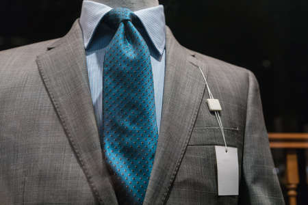 gray suit: Close-up of a light gray checkered jacket with striped blue shirt, teal tie and a blank white tag on the left lapel  Stock Photo