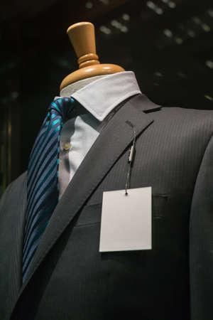 스트라이프 블루 넥타이와 왼쪽 옷깃에 빈 흰색 태그 어두운 회색 스트라이프 재킷의 근접